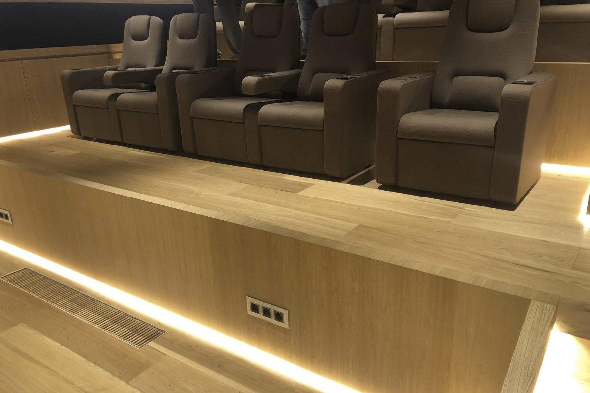 Instalación de tarima tricapa de roble forrado de huella y tabica en cine de vivienda unifamiliar de lujo